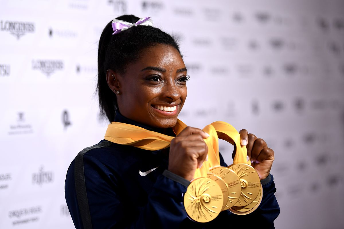 Simone Biles poses for photos with her multiple gold medals during day 10 of the 49th FIG Artistic Gymnastics World Championships at Hanns-Martin-Schleyer-Halle on October 13, 2019 in Stuttgart, Germany.