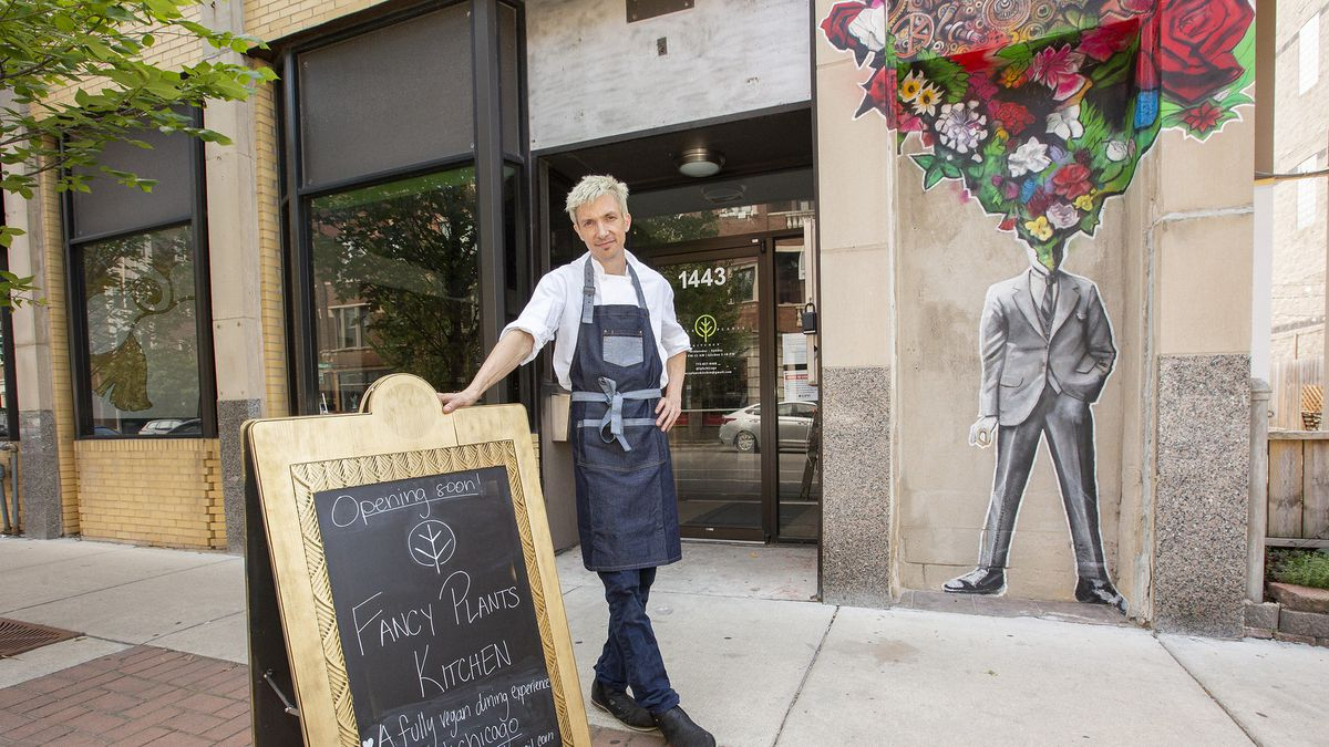 a chef stands beside a chalkboard outside his restaurant
