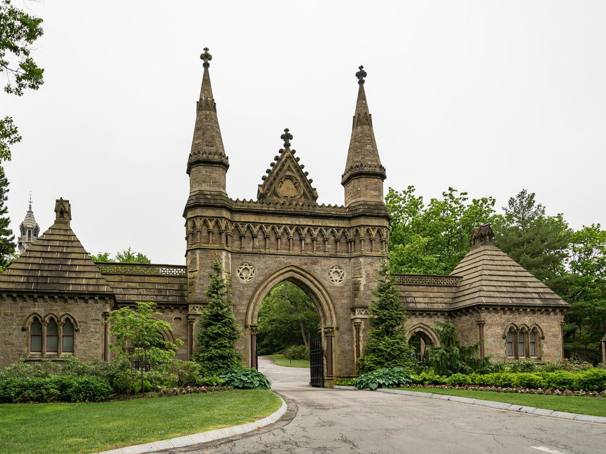 An arched entryway to a cemetery, with two small towers poking up from either end of the arch.