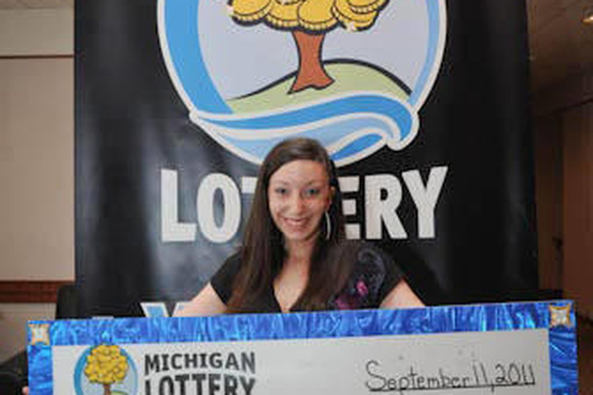 FILE - In this March 8, 2012 file photo provided by the Michigan Lottery, Amanda Clayton holds her $1 million lottery check. Clayton, who continued to get food stamps after winning a $1 million lottery jackpot, has been charged with welfare fraud. The Mic