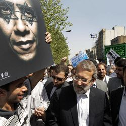 Iranian parliament speaker Ali Larijani, center, attends a protest after the Friday prayer, on Friday, Sept. 14, 2012, while a worshipper holds up a poster of US President Barack Obama, as part of widespread anger across the Muslim world about a film ridiculing Islam's Prophet Muhammad.