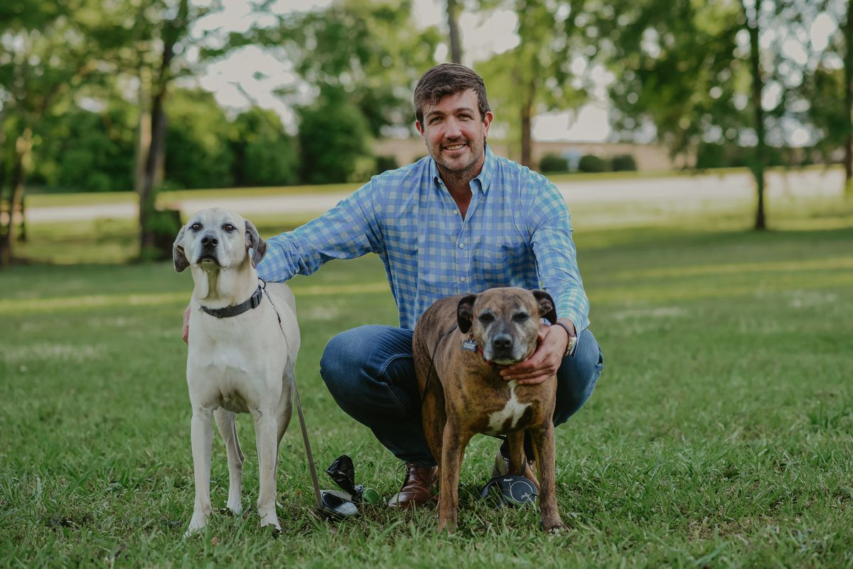 Brock Nix, owner of Common Roots Farmers Market, smiles as he squats on the grass with his two mixed-breed, medium-sized dogs.
