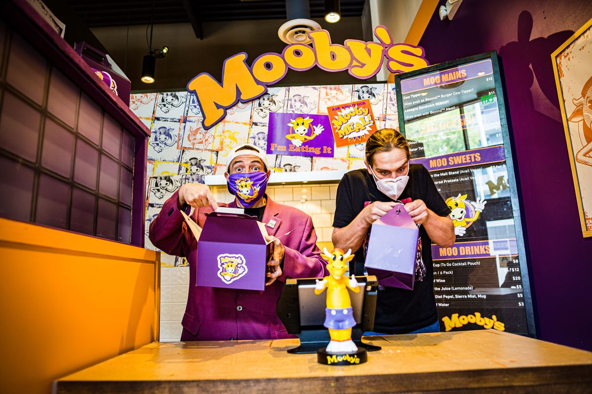 Kevin Smith and Jason who played Silent Bob and Jay respectively stand inside the bright purple and yellow dressing of Mooby's fast food burger spot