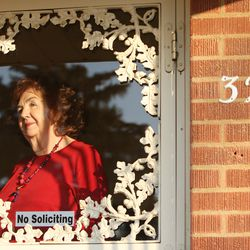 Charlotte Jensen, 77, looks out of the front door at her home in Salt Lake City Nov 26, 2013.