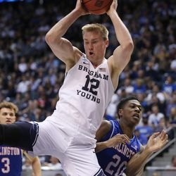 Brigham Young Cougars forward Eric Mika (12) grabs a rebound over Texas-Arlington Mavericks forward Julian Harris (20) as BYU and University of Texas at Arlington play in NIT basketball action at the Marriott Center in Provo, Utah on Wednesday, March 15, 2017.