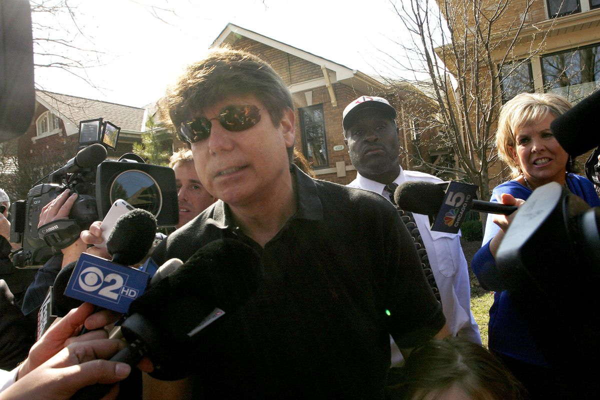 Convicted former Illinois Governor Rod Blagojevich (L) walks toward a waiting car as he holds a news conference outside his home March 14, 2012, in Chicago.