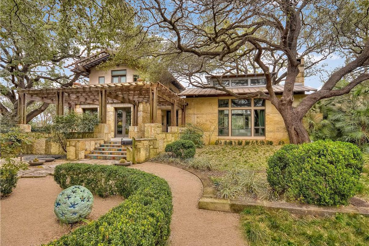 Large limestone and wood-frame house with manicured front grounds, walkway, lots of trees