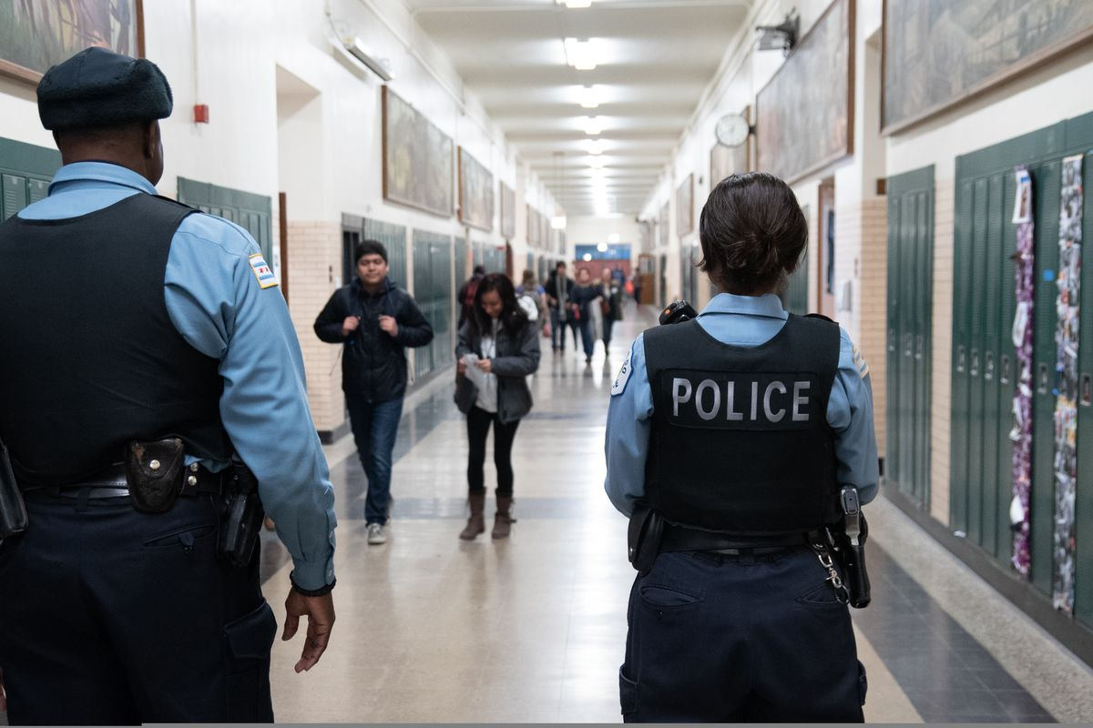Campus police officers walk the halls of Lane Tech High School in Chicago.