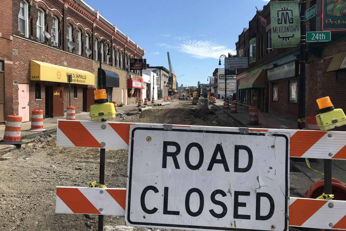 """A """"Road Closed"""" sign in front of a road with the street torn up. Businesses in brick buildings line either side of the street."""