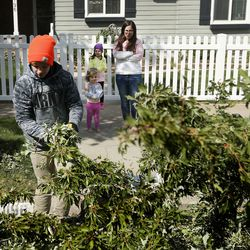 Lindsey Stephens, center, and daughters Eleanor, 5, and Rose, 3, watch as members of the Bountiful 7th Ward haul away branches from her yard in Bountiful on Wednesday, Sept. 9, 2020. The massive windstorm that took out thousands of trees from Cache County to Utah County on Tuesday left nearly 200,000 customers without power.