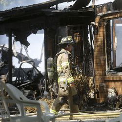 A firefighter works at the scene of a house fire in Millcreek on Thursday, July 9, 2020. The fire is the third structure fire on this block in a week, and the second fire at the same house. Four houses in total have been damaged in the week's fires.