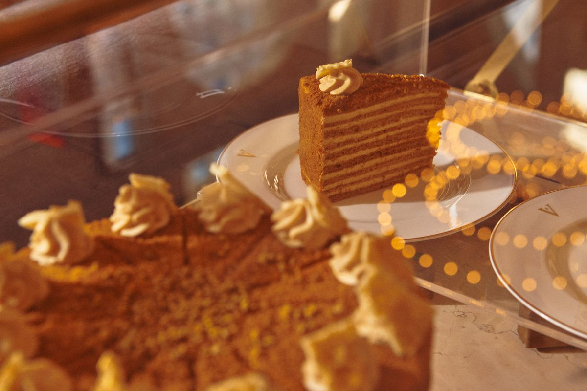 A case with an amber-colored, multi-layered slice cake, with a bigger cake in the foreground.