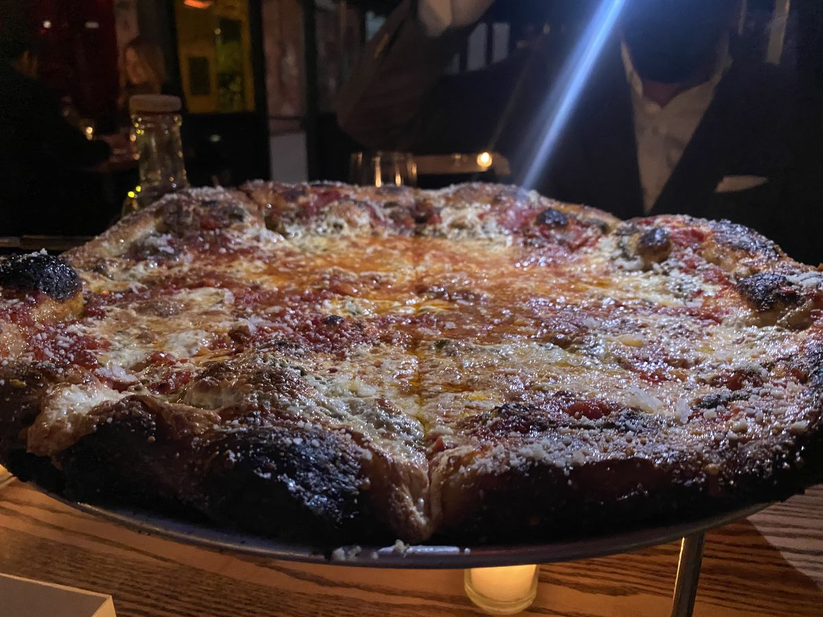 A blue light shins down upon a whole mustard pie at Momofuku Ko; the pizza sits on a metal rack above the table