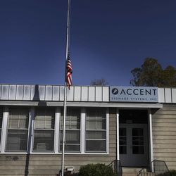 An informal memorial for shooting victims stand at the base of a flagpole, with the flag at half-staff, outside Accents Signage Systems, Inc. in Minneapolis, Minn. Saturday, Sept. 29, 2012.  Six people, including the suspected gunman, were shot to death Thursday afternoon at Accent Signage Systems. Police say Andrew Engeldinger, 36, was fired from the company that afternoon and responded by fatally shooting others there before he turned the gun on himself.