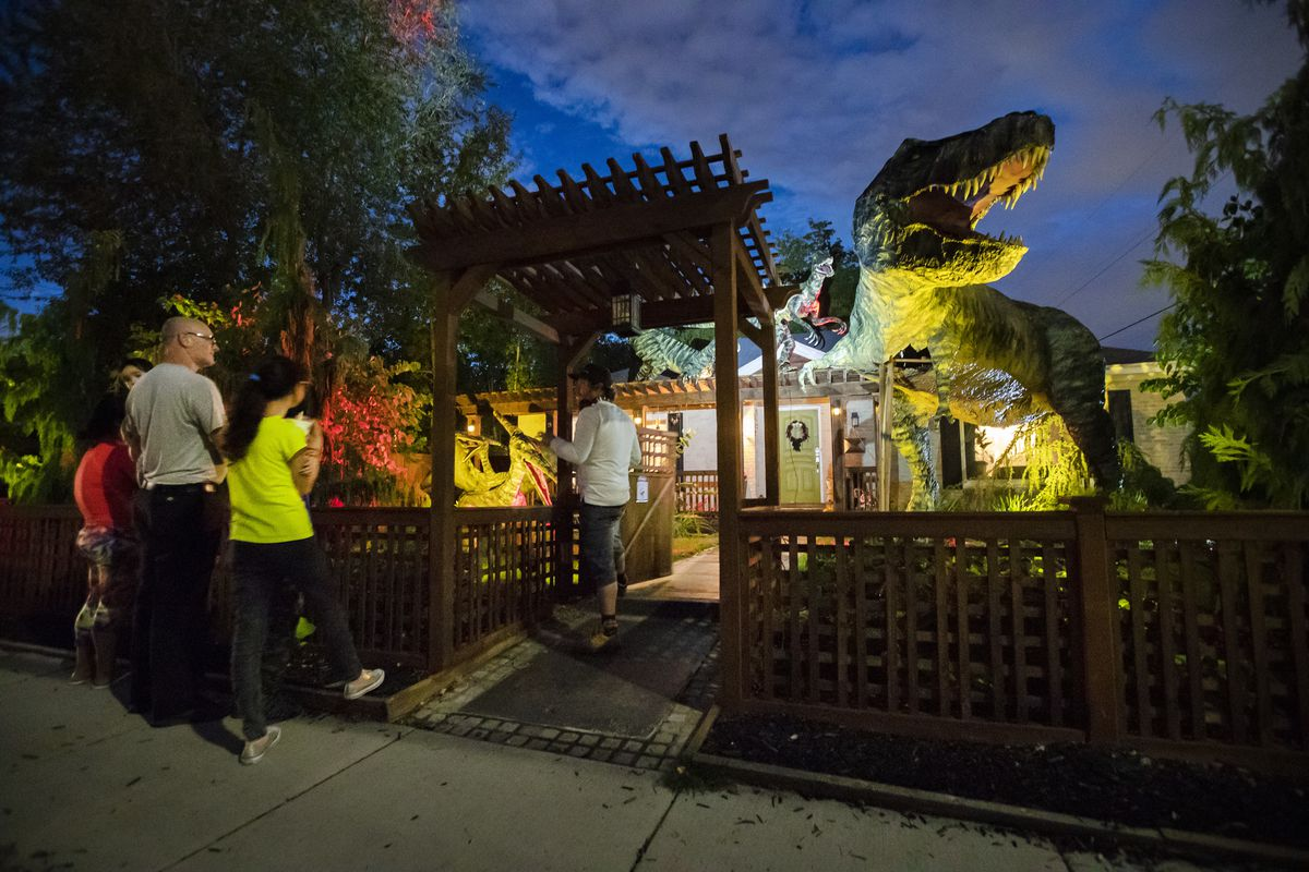 The Darcy family talks with Ammon Smith about the dinosaur display he created for Halloween in the front yard of his home in Salt Lake City on Wednesday, Oct. 3, 2018.
