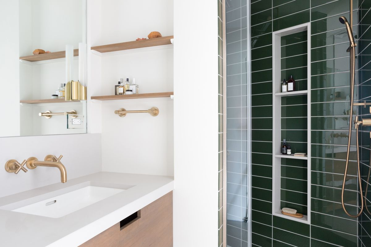 Modern bathroom with white sink, brass fixtures, and a nearby shower lined with forest green tiles.