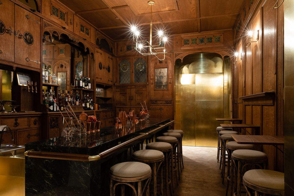A dim room with a bar to the left and round stools.