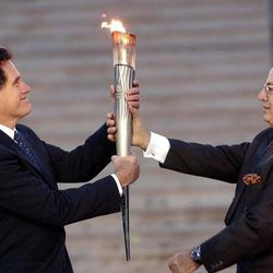 SLOC member Mitt Romney receives the Olympic torch from Hellenic Olympic Committee President Lambis Nikolaou in Athens, Greece, Dec. 3, 2001.