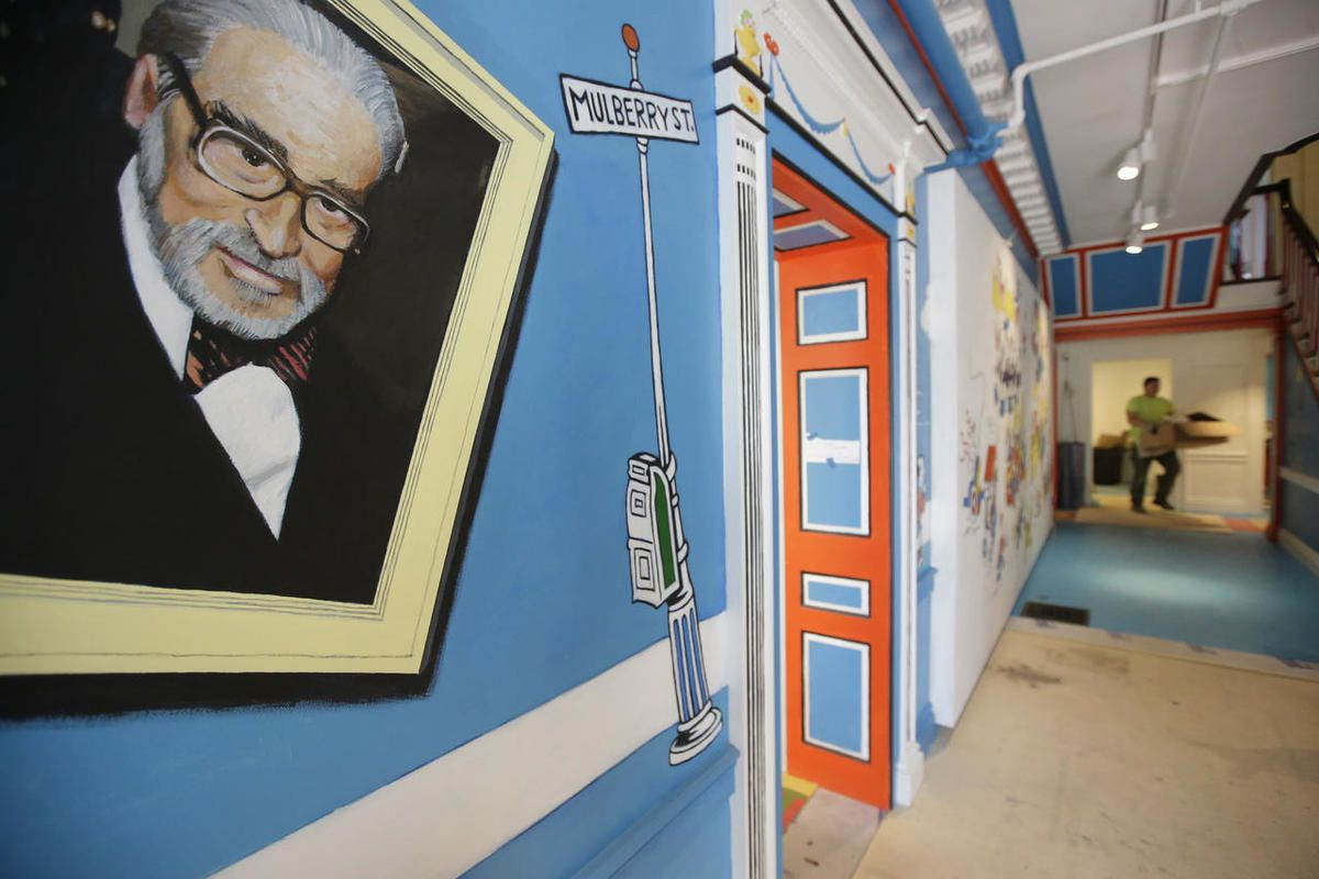 In this May 4, 2017, photo a mural that features Theodor Seuss Geisel, left, also know by his pen name Dr. Seuss, rests on a wall near an entrance at The Amazing World of Dr. Seuss Museum, in Springfield, Mass. The new museum devoted to Dr. Seuss opened o