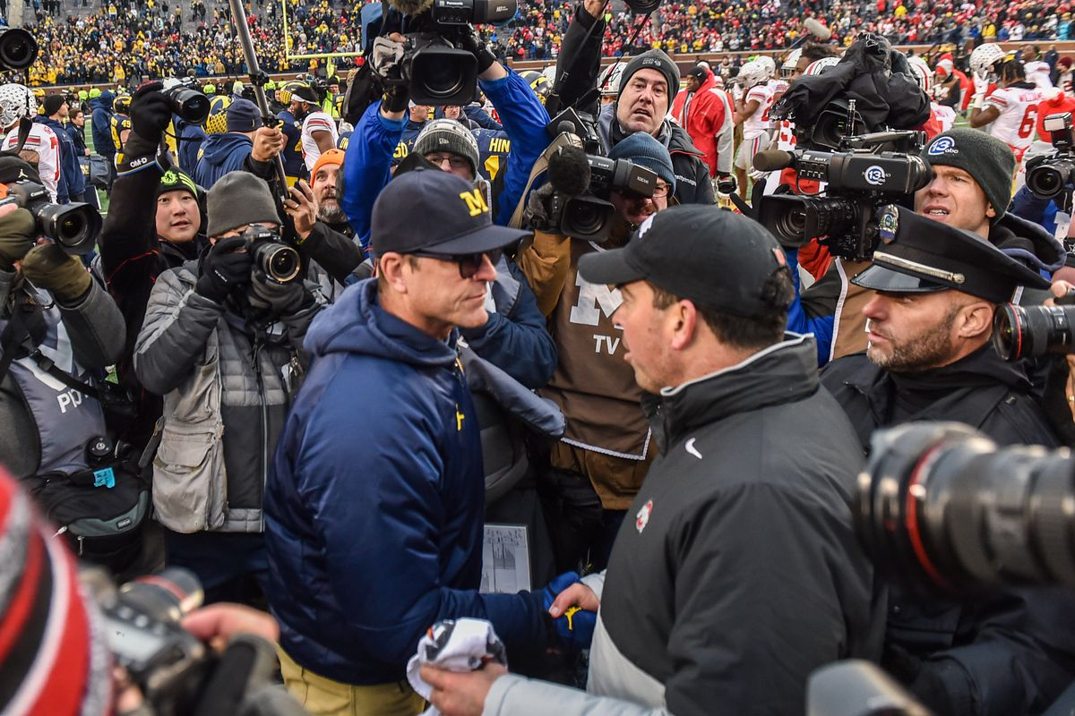 Head Coach Ryan Day of the Ohio State Buckeyes shakes hands with Head Coach Jim Harbaugh of the Michigan Wolverines after a college football game at Michigan Stadium on November 30, 2019 in Ann Arbor, MI.