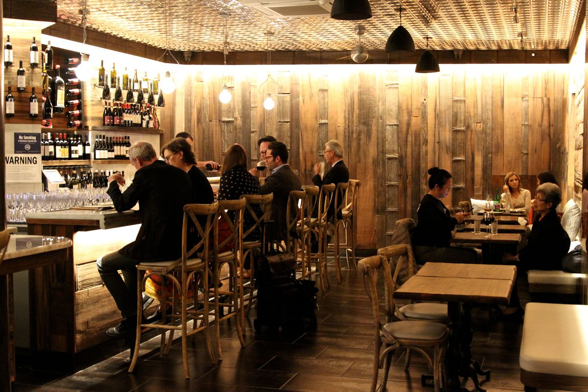 A dimly lit, warm wine bar filled with people