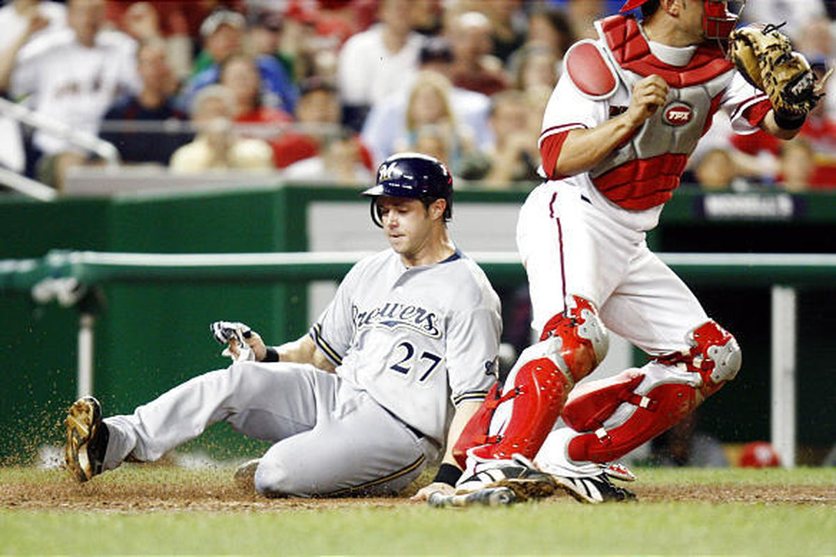 Milwaukee Brewers' Frank Catalanotto is safe at home plate as he slides past Washington Nationals catcher Wil Nieves during the seventh inning of a baseball game.