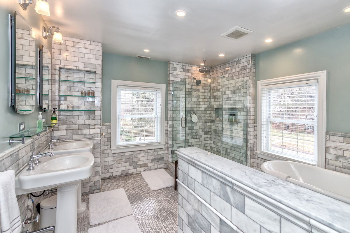 Two sinks across from a walk-in glass shower and white tub are separated by a half wall, also made of marble.
