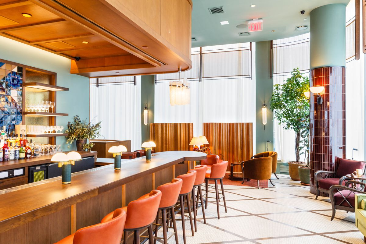 The interior of the restaurant with tangerine bar seats, wood finishes, and light blue walls.