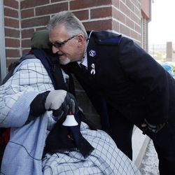 Doug Holladay, a former Salvation Army worker who is fighting terminal lung cancer, rings a bell for donations a final time in Riverdale, Thursday, Dec. 5, 2013. He gets a hug from longtime friend Raymond Young of the Salvation Army.