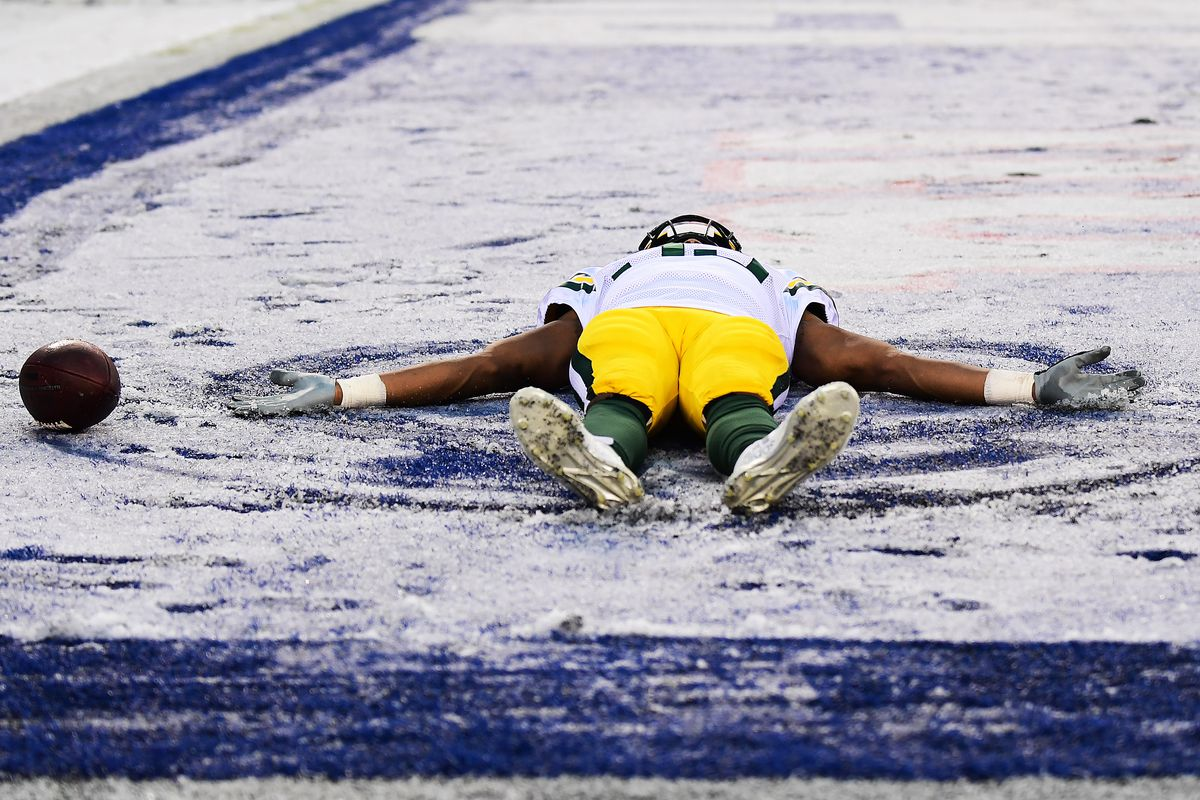 Aaron Jones of the Green Bay Packers makes a snow angel in the second half of their game against the New York Giants at MetLife Stadium on December 01, 2019 in East Rutherford, New Jersey.