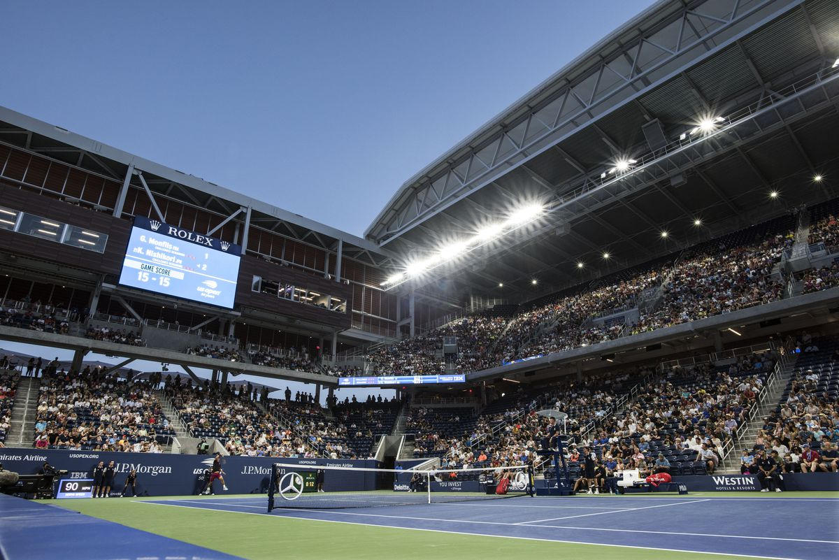 Inside a tennis stadium, with thousands of people watching a match on a green and blue tennis court.