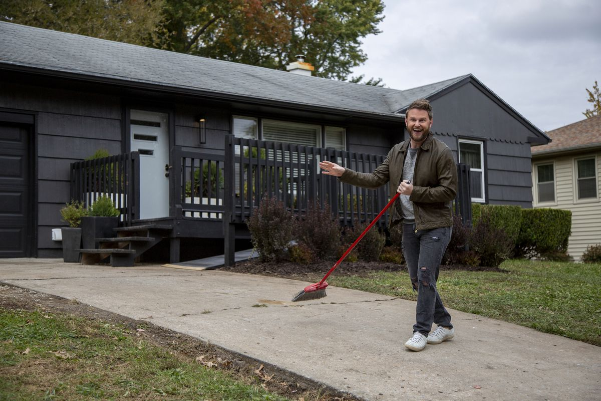 Bobby Berk stands in front of a black-painted suburban house