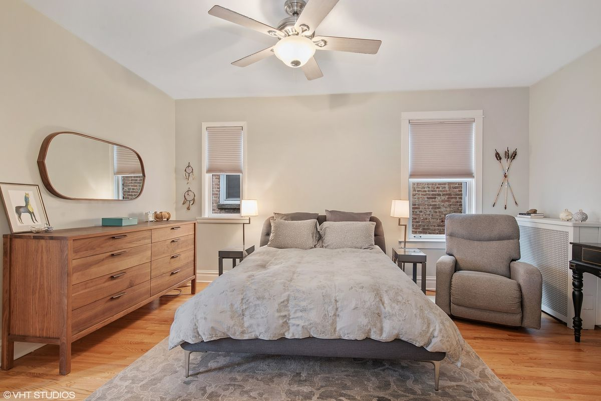 A bedroom with hardwood floors, a grey bed, a minimal wood dresser, and a fan.