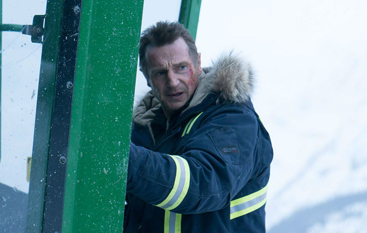 Liam Neeson climbing into a snowplow in Cold Pursuit.