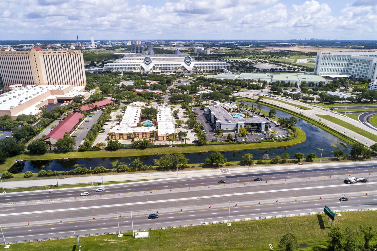 An aerial view of a large convention center and hotels with a large, many lane highway right next to it.