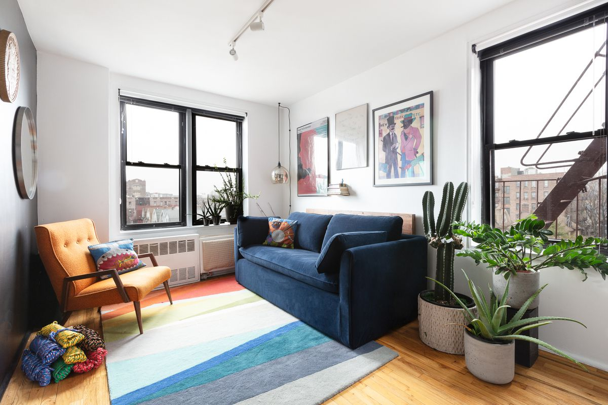 A bedroom with a small blue couch, hardwood floors, a colorful rug, and three windows.