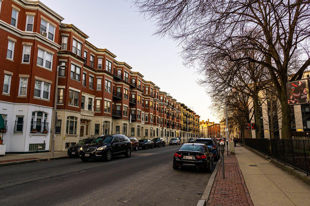 A row of four-story brick buildings along a city street.
