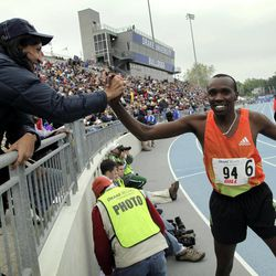 Boaz Lalang, of Kenya, celebrates with a fan after winning the men's special mile at the Drake Relays athletics meet, Saturday, April 28, 2012, in Des Moines, Iowa.