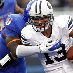 Riley Nelson (13) of the Brigham Young Cougars is brought down by Demarcus Lawrence (8) of the Boise State Broncos during NCAA football in Boise, Thursday, Sept. 20, 2012.