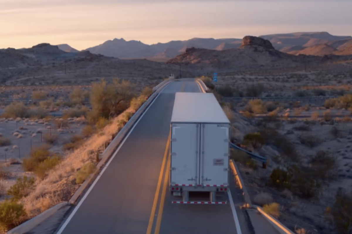 A freight truck driving away from the camera on a deserted two-lane road in the desert