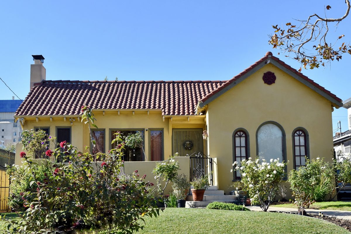A yellow stucco house with a front porch, tiled roof, and three arched windows. The house is fronted by a lawn and roses.