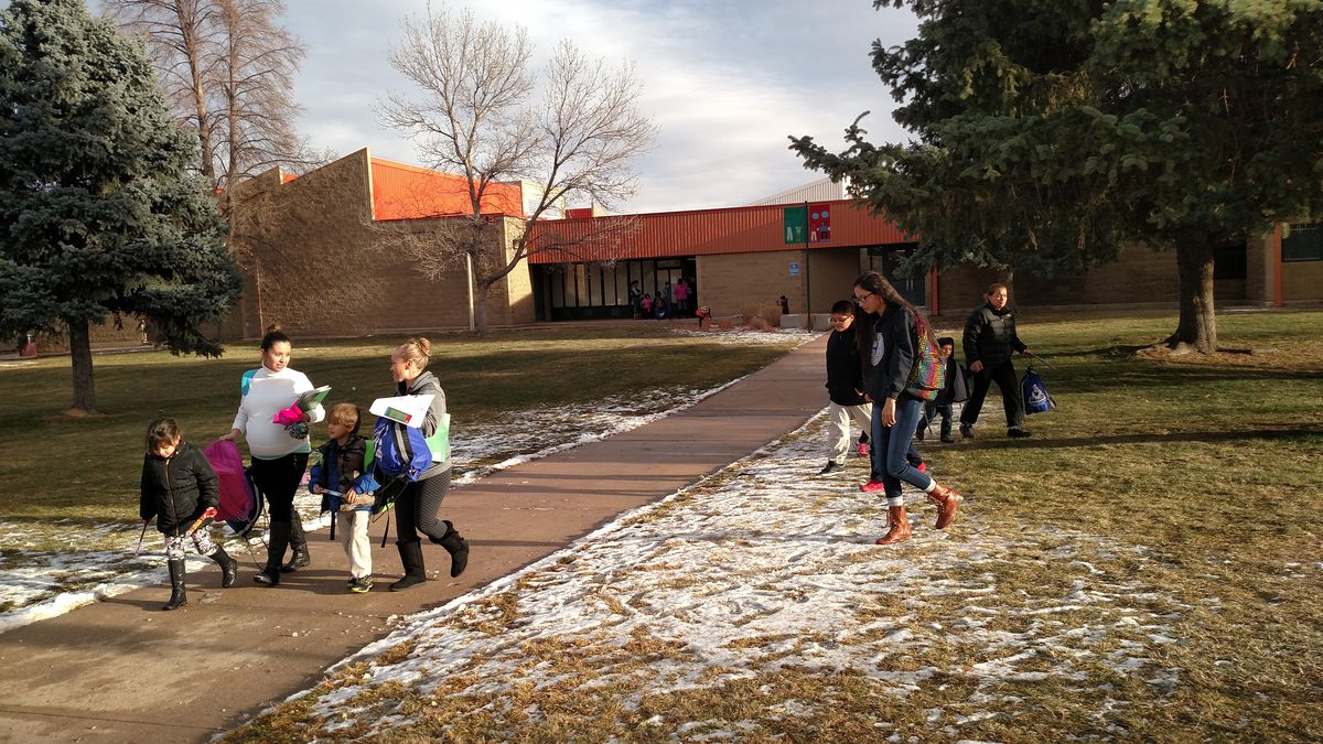 Parents pick up their children at Amesse Elementary, one of two schools that will be restarted.