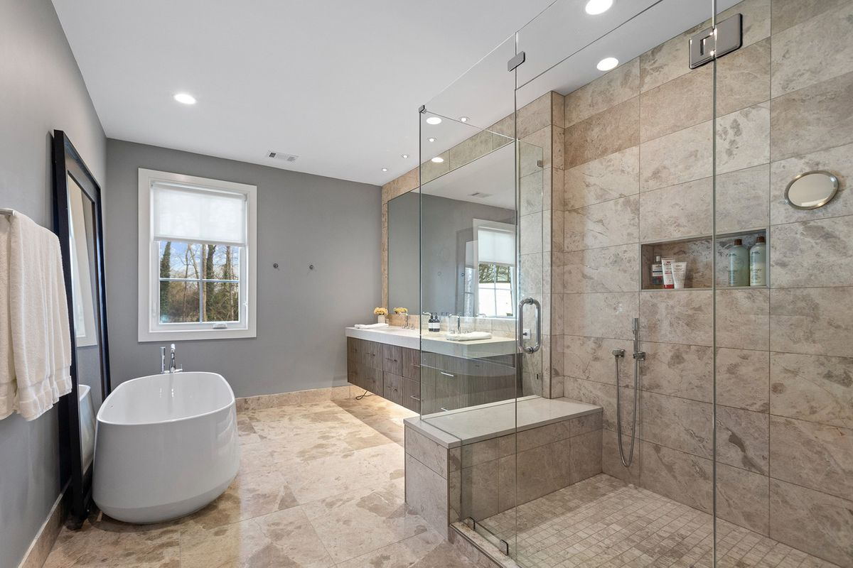 A large master bathroom with tile on the walls and floor.