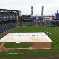 Chicago White Sox staff remove the tarp protecting the baseball diamond during the home opener at Guaranteed Rate Field, Thursday, April 8, 2021.