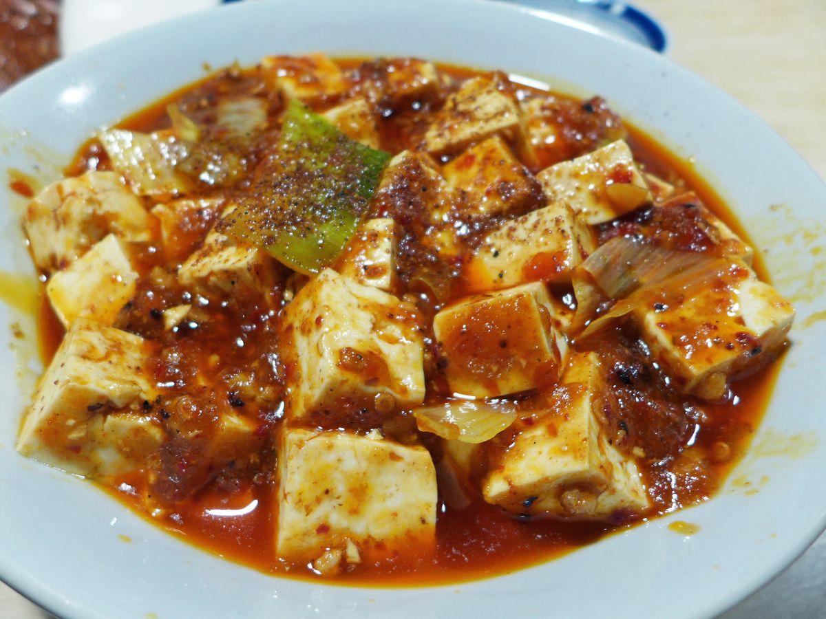 A reddish bowl of ma po tofu.