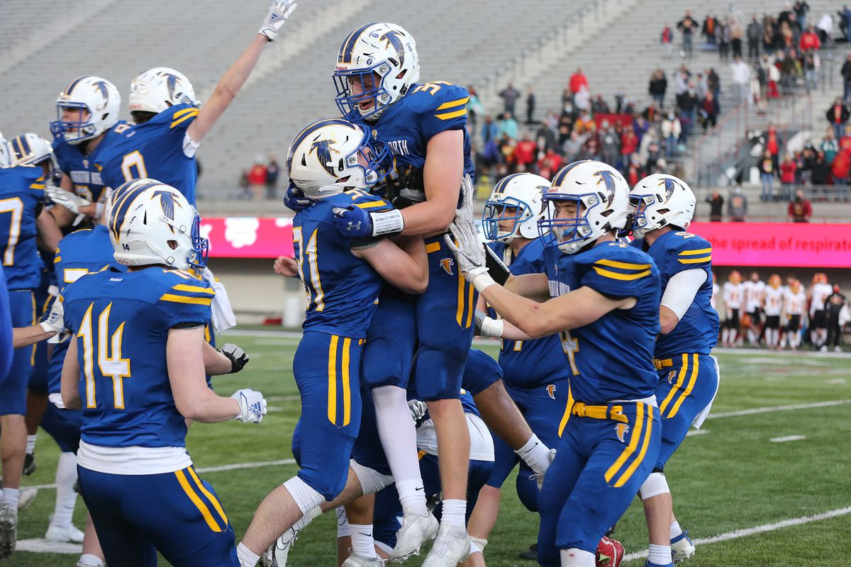 Wheaton North's Rex Kroger (34) jumps into the arms of a teammate after the Falcons beat Batavia.