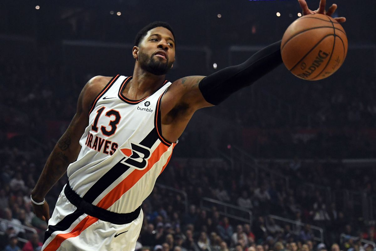 Los Angeles Clippers forward Paul George reaches to keep the ball in play against the Portland Trail Blazers during the first half at Staples Center.