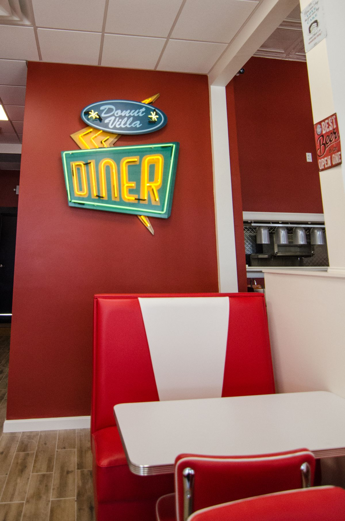 Red and white booths in a diner, with a neon diner sign on the red wall behind