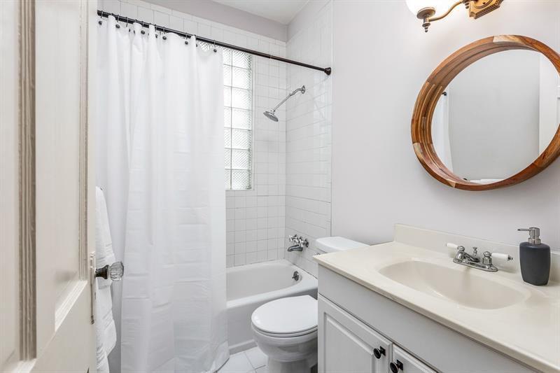 A white master bathroom with a white curtain.