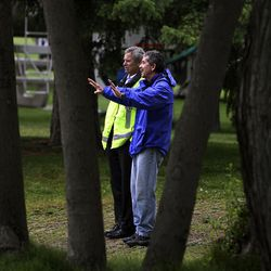 Mayor Ralph Becker, left, is briefed by Jeff Niermeyer, director of the Salt Lake Department of Public Utilities, at Liberty Park after a Chevron pipeline broke and leaked oil into the pond Saturday.